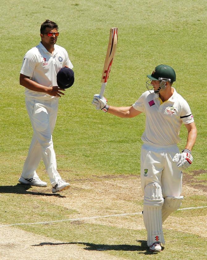 Marsh raises his bat after bringing up his half-century