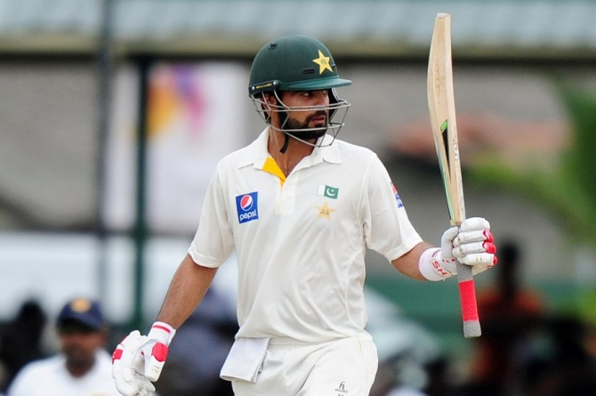 Shehzad raises his bat after bringing up his half-century