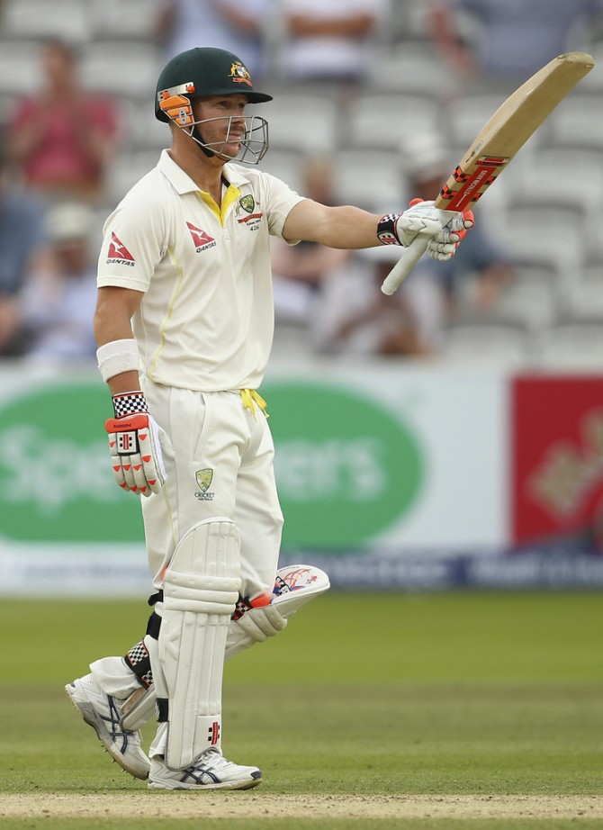 Warner raises his bat upon bringing up his half-century