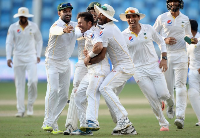 Shah is mobbed by his team-mates after leading Pakistan to victory