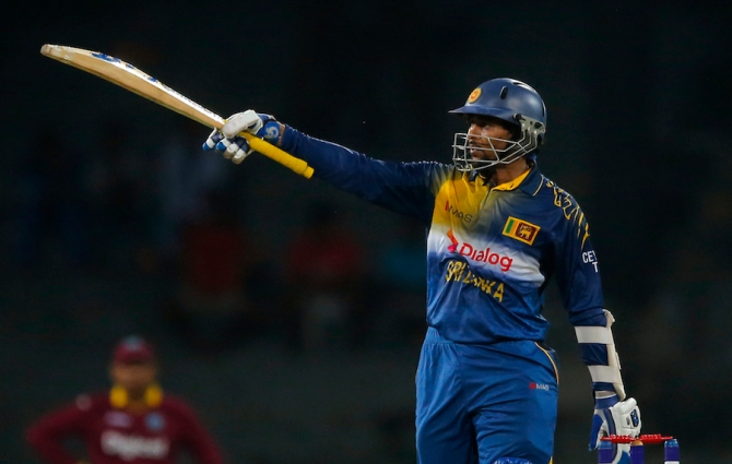 Dilshan raises his bat after scoring his half-century